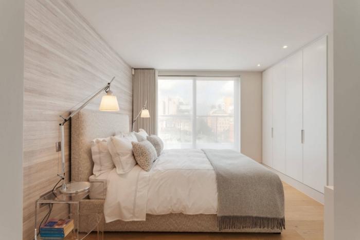 design minimaliste et simple avec revêtement mural de bois clair et garde-robe grande aux portes blanches