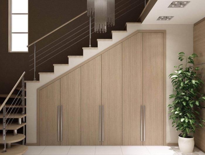 idée rangement sous escalier avec meubles de bois clair et poignées métalliques, la couleur taupe foncé dans l'intérieur