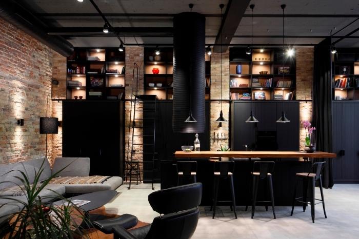 déco loft industriel avec murs en briques rouges et plafond blanc avec tuyaux noirs apparents, cuisine équipée