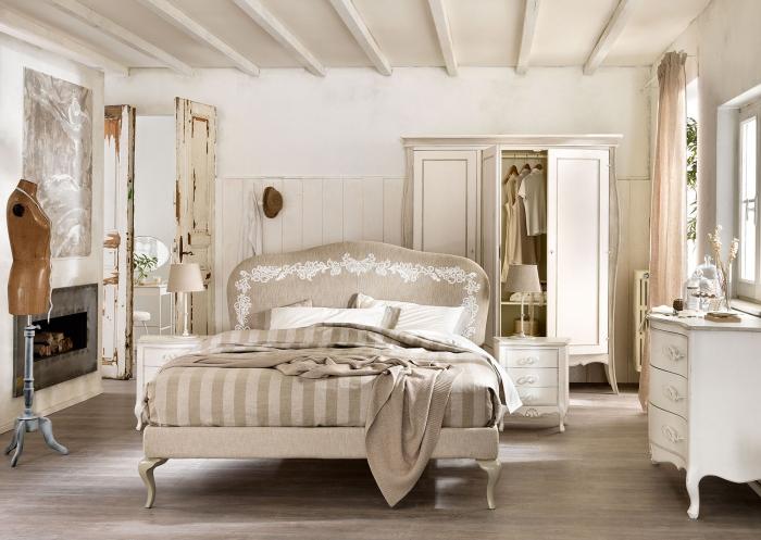 chambre adulte aux murs blancs avec meubles repeints de style shabby chic et cheminée beton