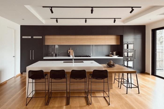 espace ouvert aux murs blancs et plafond suspendu avec sports de style industriel, cuisine noir mat et bois