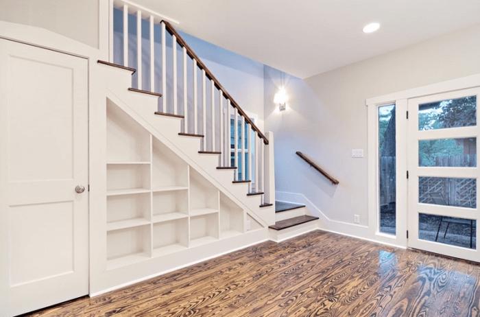 aménagement sous escalier avec étagères blanches en bois et porte, déco intérieur aux murs blancs et plancher de bois