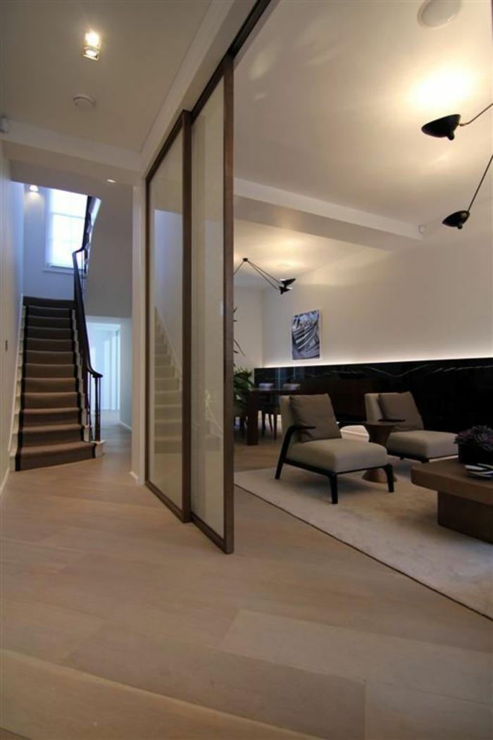 séparation chambre salon escalier, grand espace, plafond blanc, sol recouvert en parquet beige-marron, grand tapis blanc carré