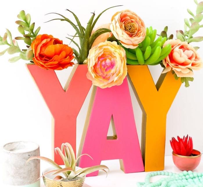 petits vases de lettres en carton décorées de peinture rose et jaune et des fleurs à l intérieur, cadeau a fabriquer pour sa meilleure amie et sa copine
