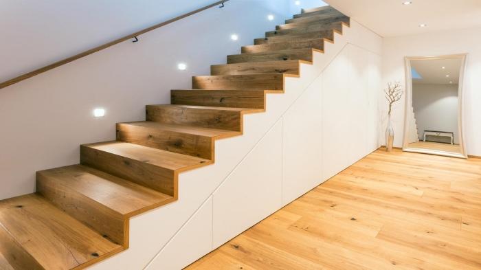 design moderne aux murs blancs et plancher de bois avec un aménagement sous escalier aux portes sans poignées