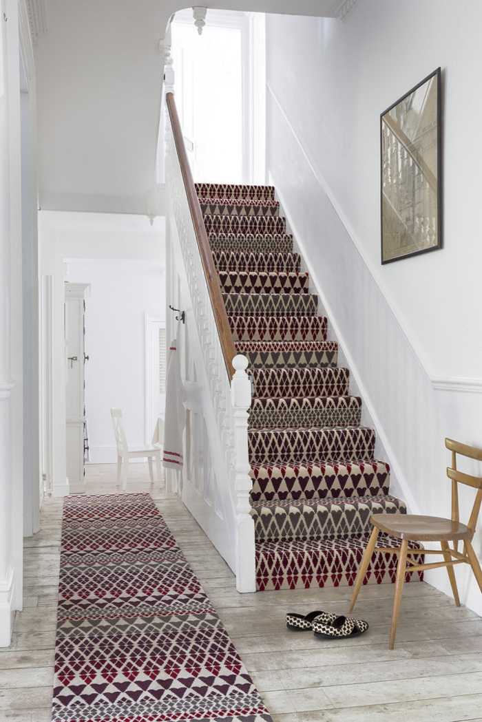 tapis d'escalier à motifs ethnique qui réchauffe la cage d'escalier monochrome aux murs et au lambris peint en blanc