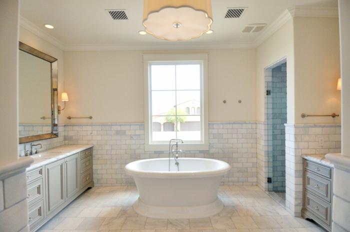 plafonnier beige, baignoire au centre de l'espace, miroir rectangulaire encadré, meubles sous vasque, travertin salle de bain