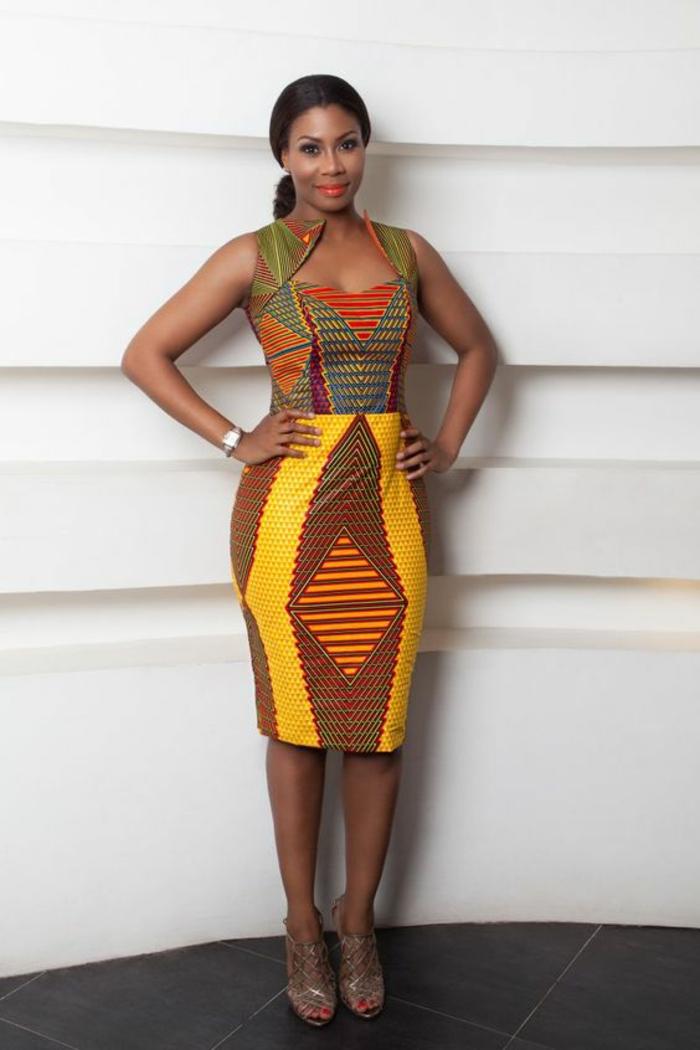 mode africaine, robe africaine sans manches, décolleté en forme de cœur, jupe sous les genoux en jaune et marron, sandales aux lacets en marron clair