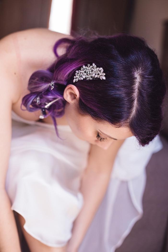 coiffure de mariée aux cheveux longs et bouclés attachés de côté, cheveux aux racines noires et pointes colorés de nuance violet et rose pastel