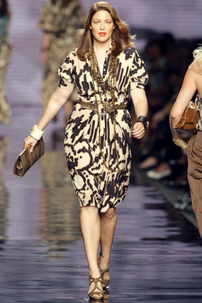 une robe amincissante aux manches courtes aux motifs ethniques, avec ceinture fine marron, longueur mi-genoux, sandales marron clair, sac pochette en marron