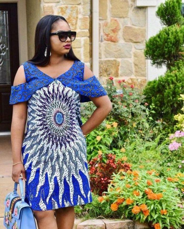 robe avec des épaules tombantes, mode africaine, grand motif africain,soleil en blanc et bleu royal, longueur au-dessus des genoux, sac à main ne bleu pastel avec des broderies de motifs fleuris en rose et bleu pastel