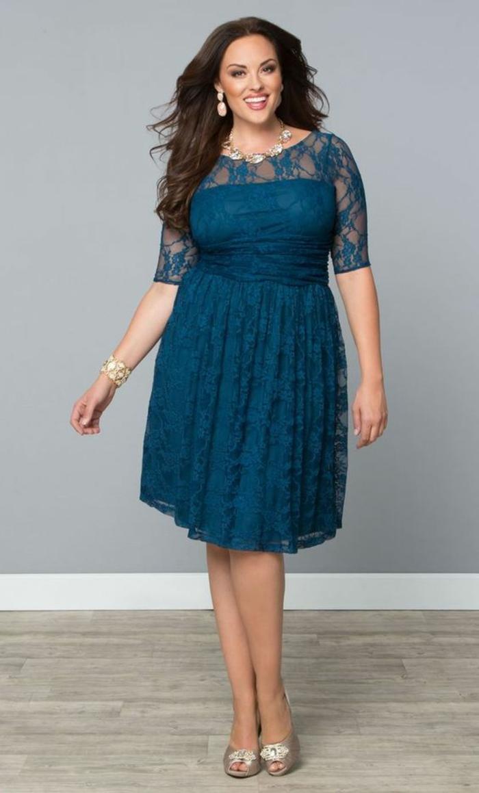 un modèle de robe amincissante en bleu pétrole, col rond, manches 3-4 en dentelle, longueur mi-genoux, chaussures aux reflets argent