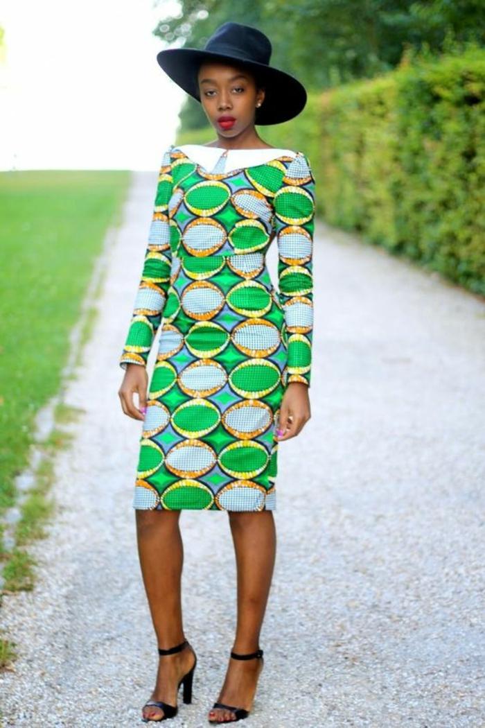 style élégant, robe africaine en vert flashy, blanc et jaune, capeline noire, décolleté bateau, manches longues, longueur moitié genoux