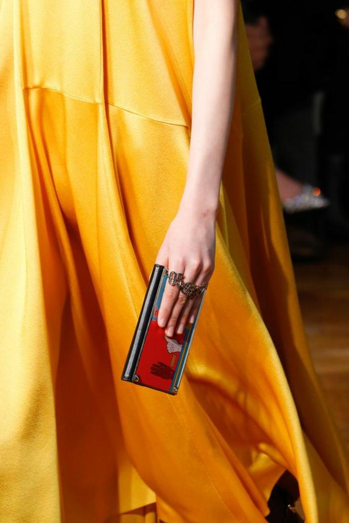 robe en orange longue et fluide, sans manches, en tissu satiné, micro sac pochette en rouge et noir, soirée chic détail choc