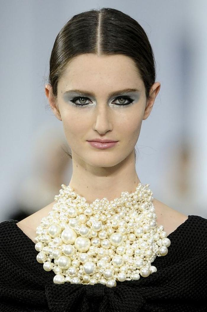 un look de Chanel, collier massif avec des perles, grandes boules, au ras du cou, bijou porté sur une robe noire avec grand nœud qui se laisse voir en dessous du collier de perles