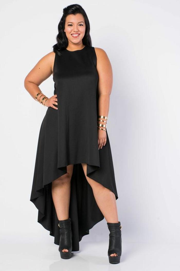 robe asymétrique en noir, en tissu satiné, tenue ceremonie femme ronde sans manches, longueur mini devant et longueur maxi derrière, chaussures noires avec des talons hauts