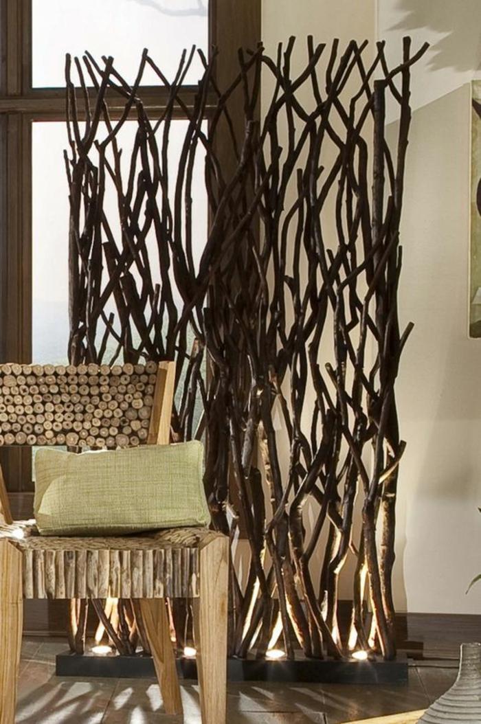 ambiance rustique avec fauteuil en bois clair massif et separateur de piece fait avec des longues banches de bois, illuminées depuis le sol avec des corps luminaires ronds, lumière blanche