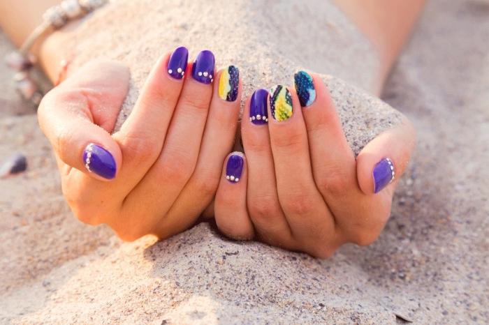 manucure à ongle en gel mi-longs avec vernis de base violet et décoration en strass sur l'annulaire