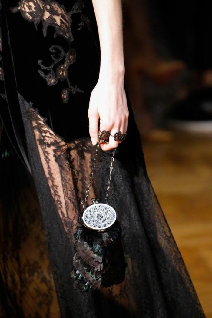 robe de soirée en dentelle noire, avec des arabesques sur la taille, mini bourse style vintage en plumes et grand fermoir en argent, thème chic et choc