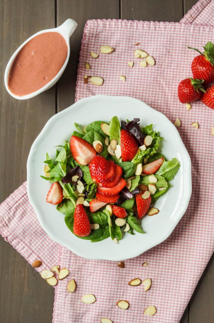 une salade verte aux fraises et aux amandes avec une vinaigrette à la fraise pour commencer en toute légèreté votre repas de saint valentin