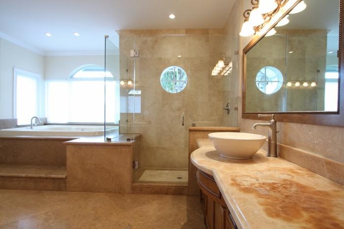 vasque à poser blanche, comptoir sophistiqué en marbre, miroir éclairé et grande baignoire surrélevée, salle de bain en travertin