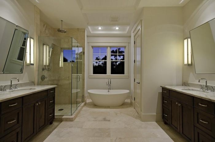 intérieur de salle de bain en couleur crème, baignoire blanche sous une grande fenêtre, carrelage travertin