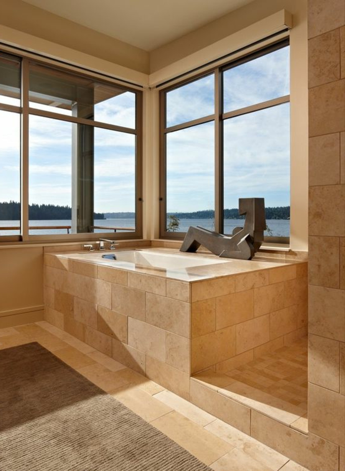 salle de bains de luxe, statuette de femme métallique, grandes fenêtres, travertin salle de bain