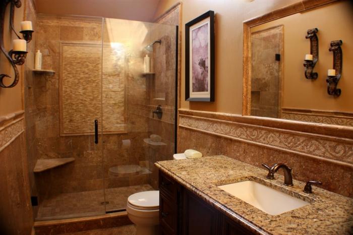pierre travertin dans la salle de bain, parois de douche en verre, bougeoirs muraux