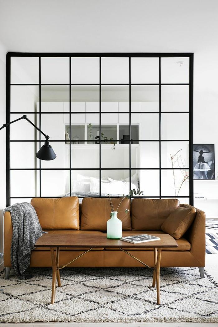 salon et chambre avec separation verriere, canapé en cuir marron, table basse rectangulaire,luminaire noir pliable en style industriel