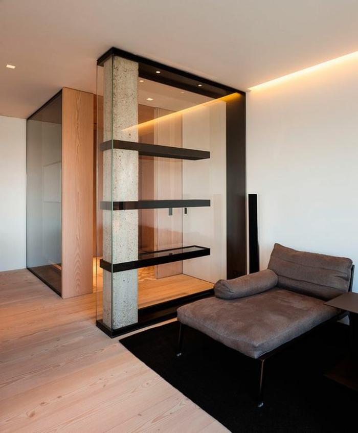 separateur de piece en pierre synthétique, étagères noires et verre, sol recouvert de parquet en PVC, canapé avec grand coussin rectangulaire et coussin long en forme arrondie