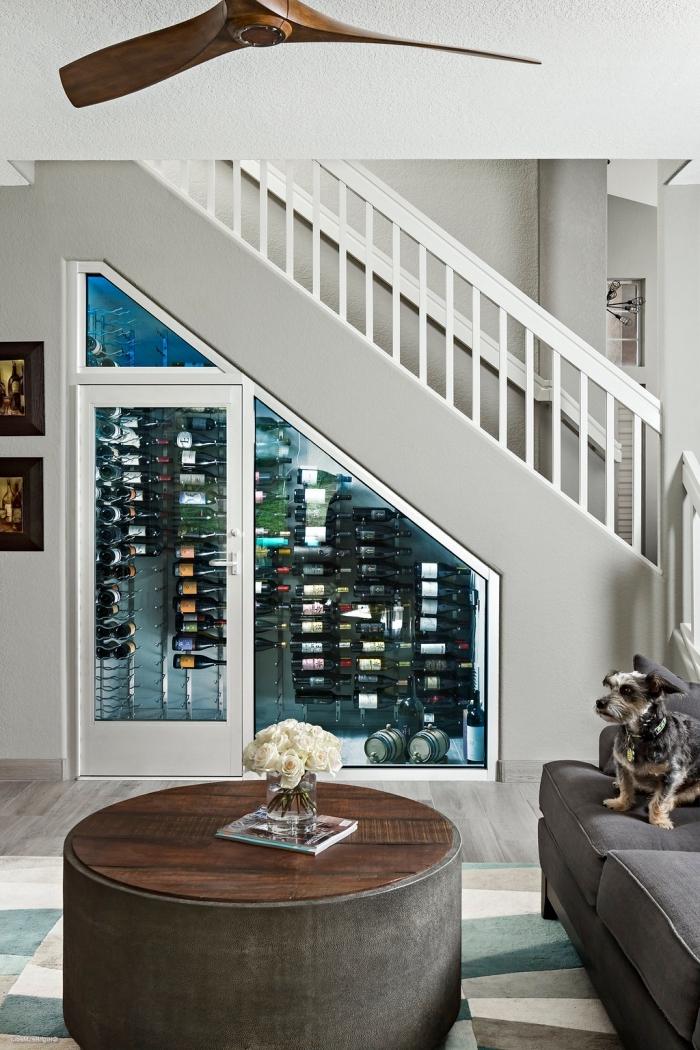 rangement sous escalier avec porte de bois et verre pour stocker les bouteilles de vin