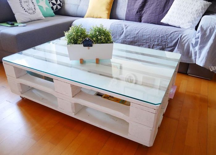 modele de table en palette basse repeint en blanc sur roulettes et plateau en verre, canapé d angle gris