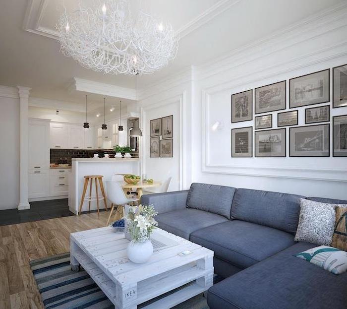 table en palette repeinte en blanc, canapé d angle gris, tapis gris et noir, parquet marron clair, murs blancs, lustre original