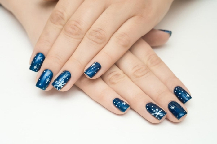 idée manucure pour Noel avec vernis gel bleu foncé et dessin à design étoiles et flocons de neige blanches