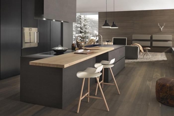 cuisine ouverte vers le salon au plafond blanc et plancher de bois stratifié foncé, cuisine noir mat avec comptoir de bois