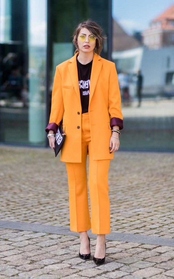 un tailleur pantalon femme de couleur orange tangerine et de coupe masculine, veste structurée combinée avec un t-shirt graphique pour une allure assurée