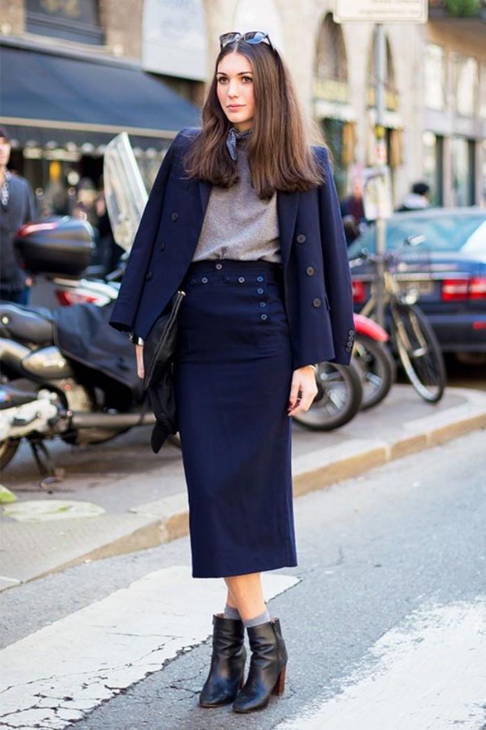 silhouette élégante en tailleur jupe femme de couleur bleu marine portée de façon décontracté en combinaison avec un t-shirt gris et des chaussettes grises qui dépassent les bottines
