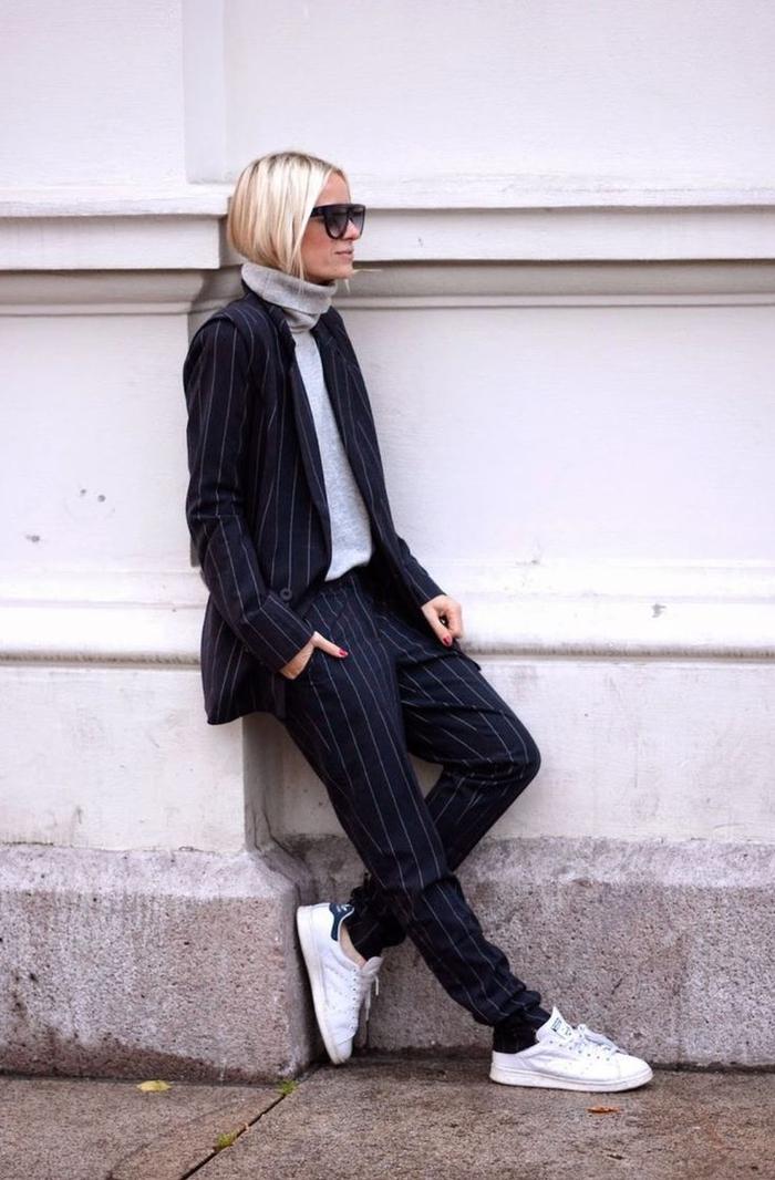 un costume femme de coupe garçonne à fines rayures porté de façon ultra décontractée avec des baskets blancs et un large pull gris à col roulé