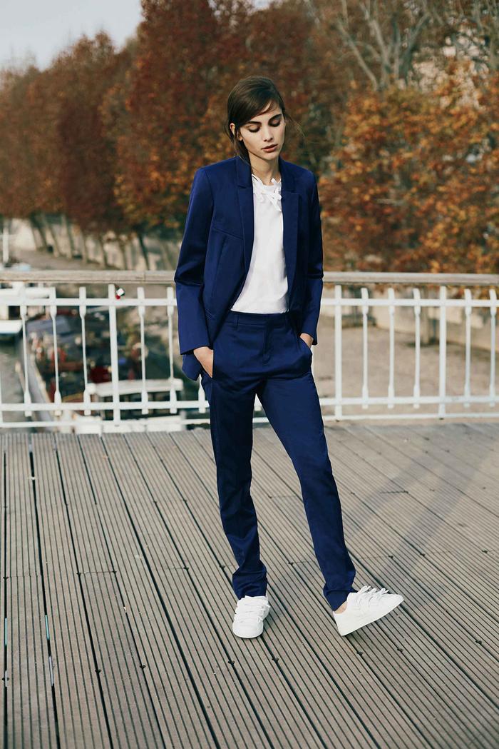 look masculin féminin avec un tailleur pantalon femme couleur bleu marine, des baskets blancs et une blouse blanche