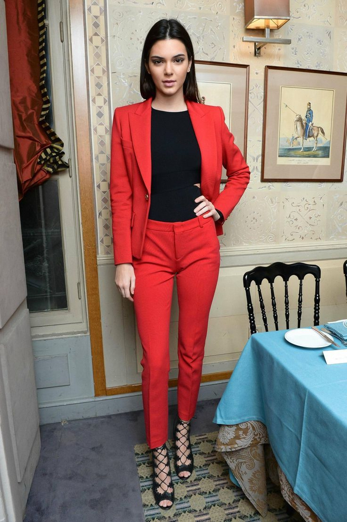 un costume femme rouge de coupe simple flatteuse rendu moins formel par son association aux sandales à lacets montants croisés