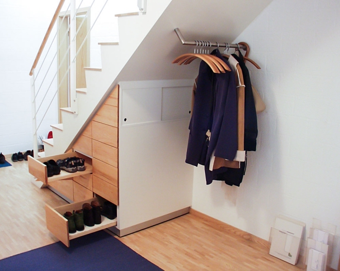 meuble sous pente pour stocker les chaussures et les vestes, couloir aux murs blancs avec meubles de bois