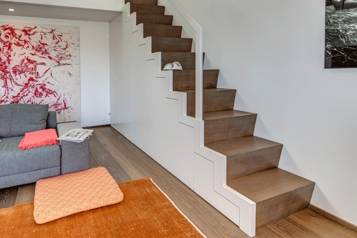 déco avec aménagement sous escalier, salon ouvert aux murs blancs avec grande peinture abstraite de couleurs rouge et blanc
