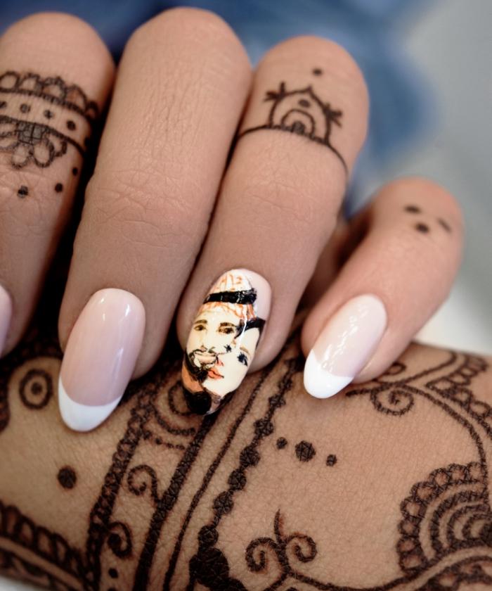 jolies mains féminines avec art corporel en henné noir et manucure française avec dessin couple sur l'annulaire