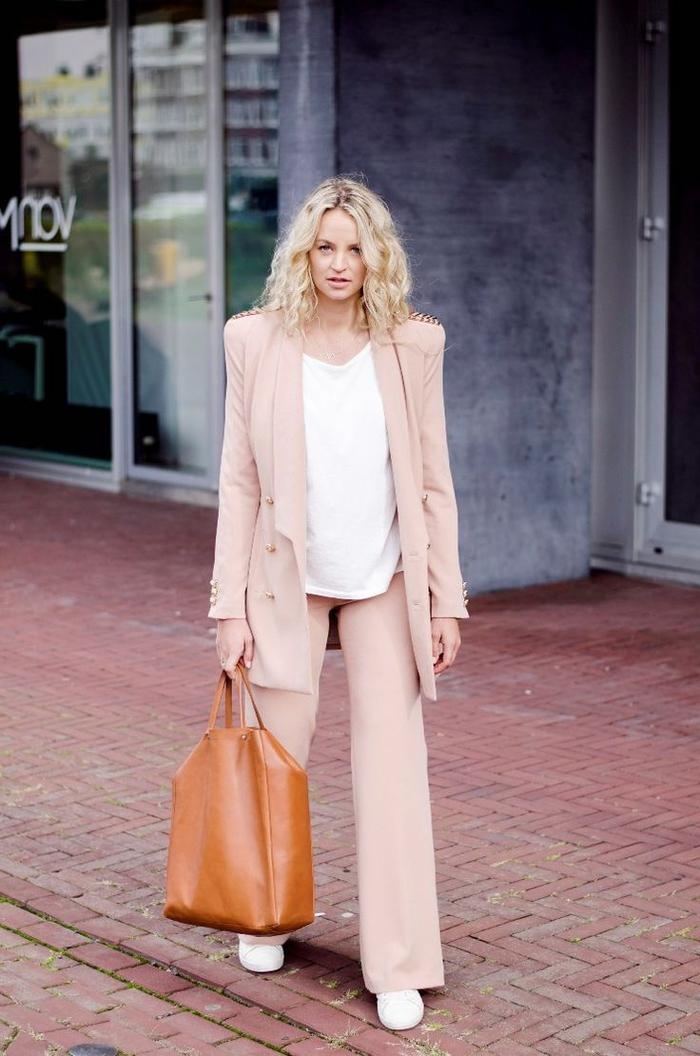 comment adopter la tendance power dressing en smoking femme de couleur rose poudré, un pantalon de tailleur fluide associé à un blazer clouté de la même couleur pastel et à un top aérien blanc