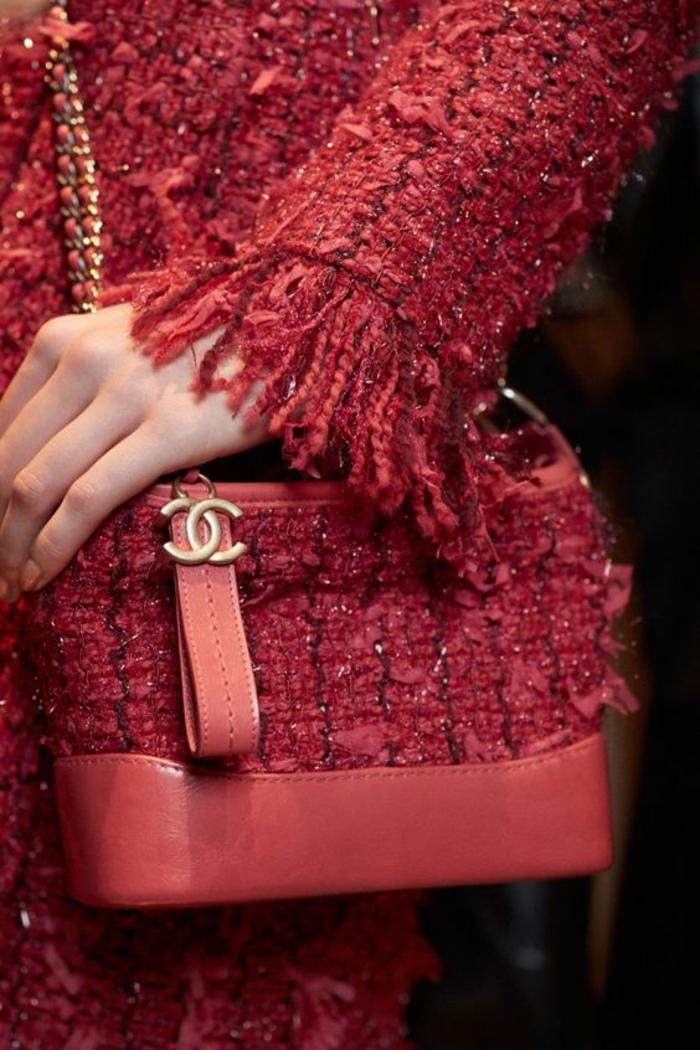 un look Chanel, veste et jupe en rose sorbet, micro sac Chanel avec le logo, franges sur les ourlets des manches, thème chic et choc