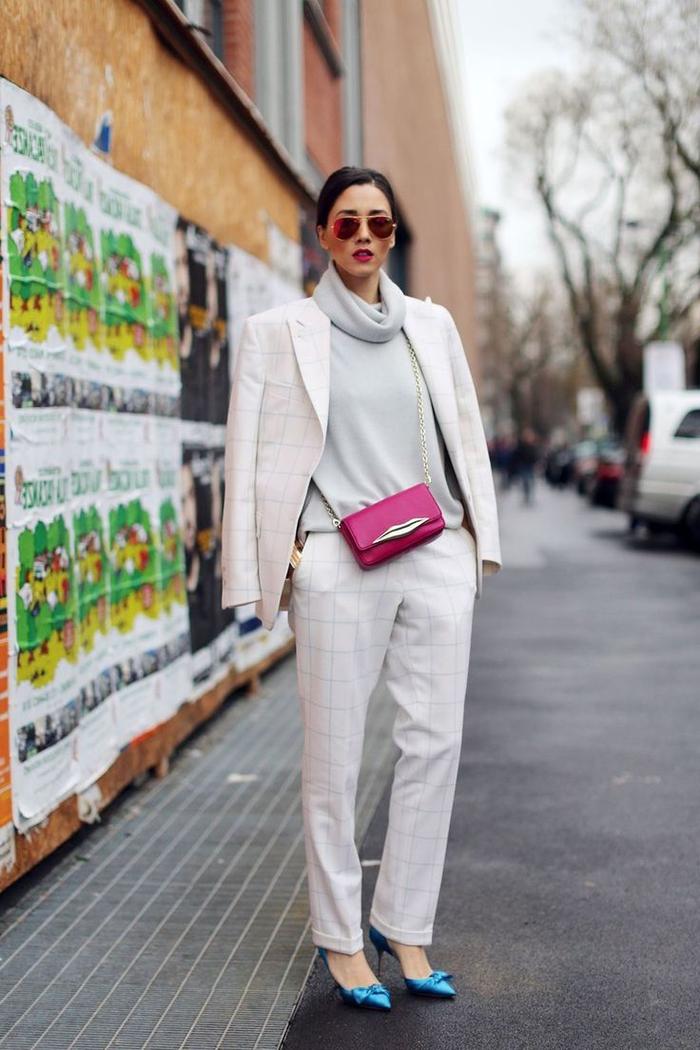 vision chic et romantique en tailleur femme à carreaux blanc porté de façon décontracté avec un blazer sur les épaules sur un pull cachemire et combiné des accessoires flashy