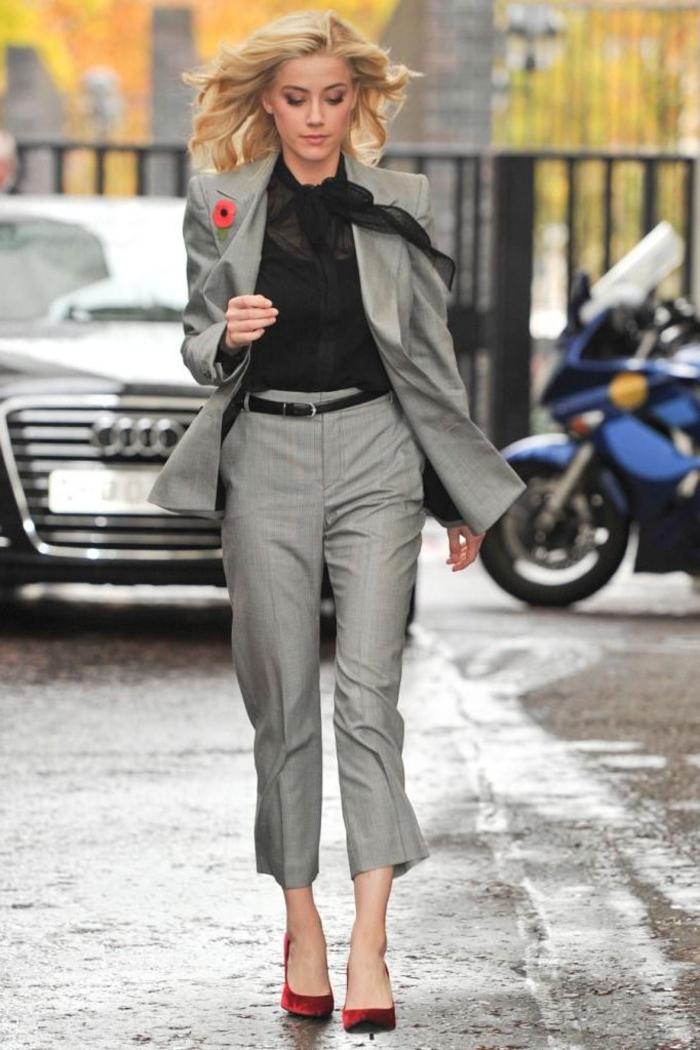 un tailleur pantalon femme gris féminisé par une chemise en voile à col noeud et un petit accent floral au revers