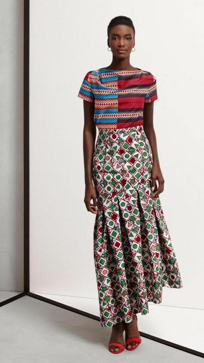 femme avec jupe asymétrique plissée, mode africaine, top avec des manches courtes avec des larges rayures horizontales, jupe avec des motifs ronds et triangles en rouge et vert