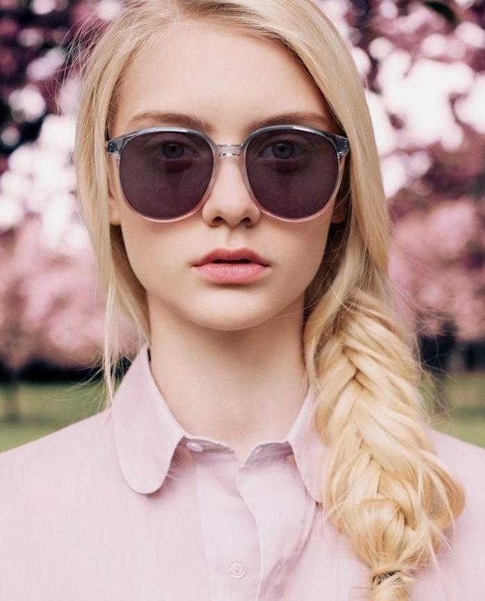 coiffure natte de coté avec des meches libres style décoiffé, chemise femme rose, lunettes de soleil