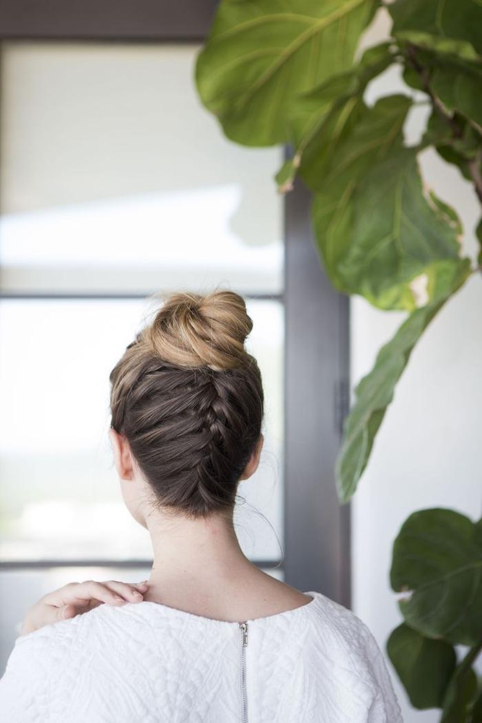 un joli chignon avec tresse inversée qui met en valeur le balayage blond et les mèches subtiles